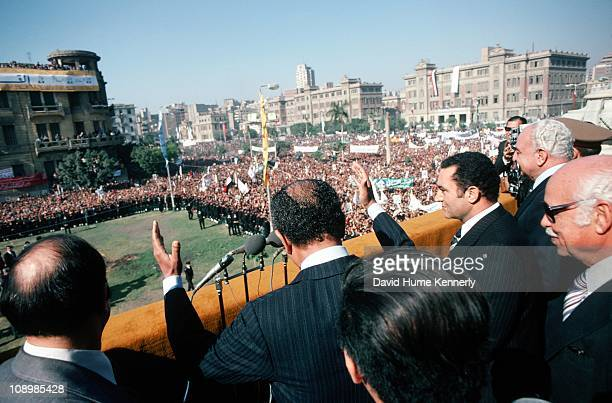 Egypt's President Anwar al Sadat raises his arms in greeting to supporters gathered upon the presidential grounds in Cairo during a rally held in...