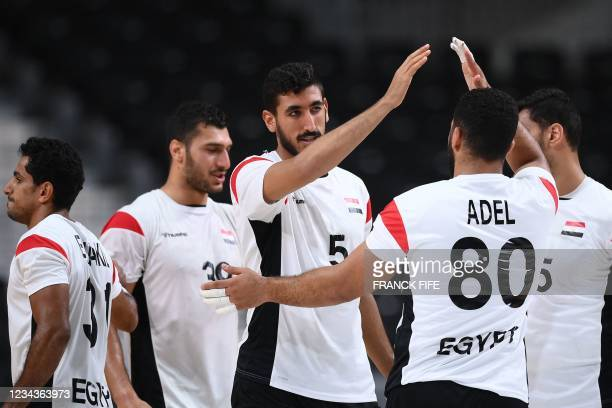 Egypt's right back Yahia Omar and teammates celebrate their victory after the men's preliminary round group B handball match between Egypt and...