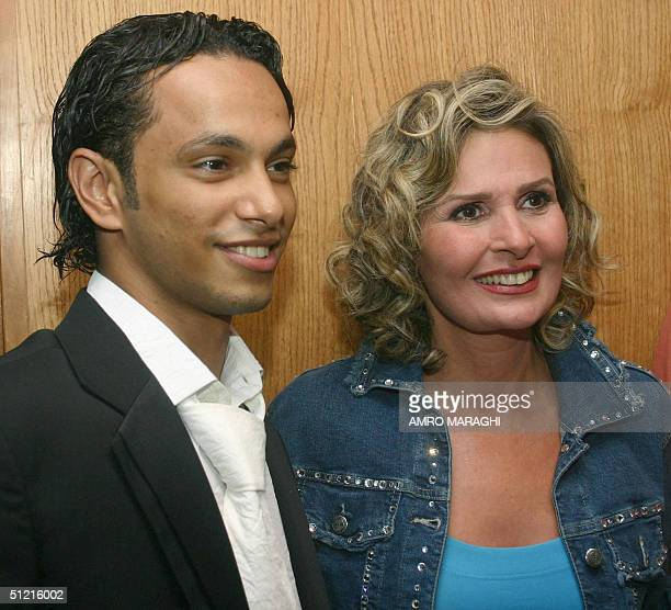 Egypt's top film Star Yusra poses with young actor Ahmad Yahya upon their arrival at a movie theatre in Cairo 22 August 2004 to attend the premiere...