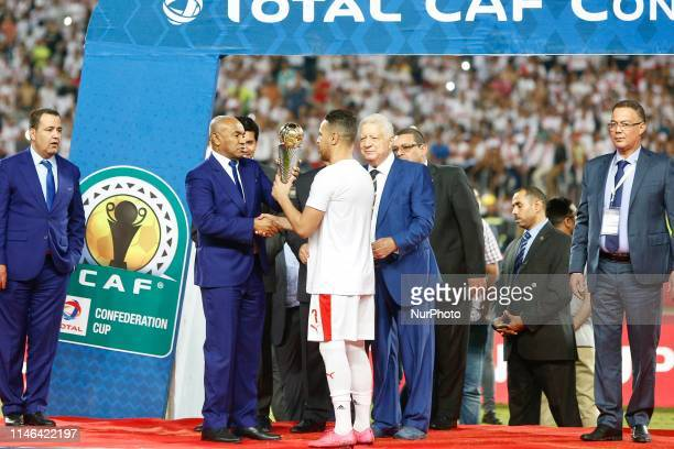 Egypt's Zamalek player Hazem Emam receives the trophy from the president of the African Football Federation Ahmed Ahmed after they won the CAF...