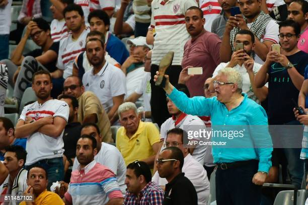 Egypt's Zamalek president gestures as he holds a shoe during the football match with Al Ahly Tripoli player in the African Champions League group...