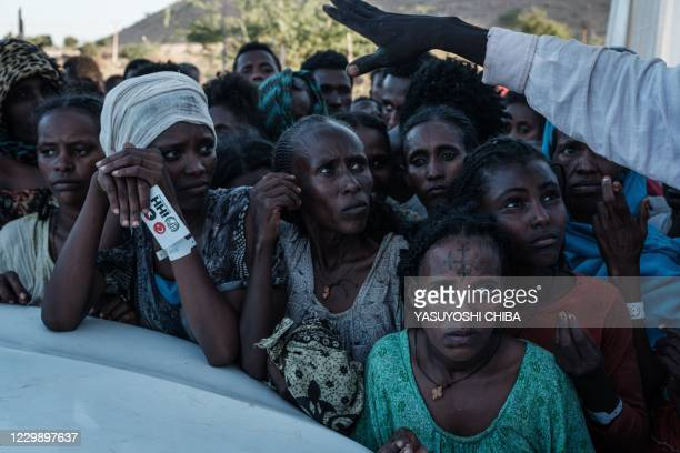 Ehiopians, who fled the Ethiopia's Tigray conflict as refugees, wait for food distribution in front of a warehouse at Um Raquba refugee camp in...