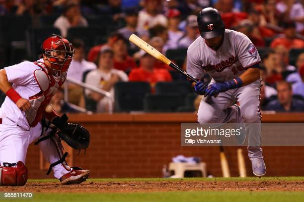 Ehire Adrianza of the Minnesota Twins is hit by the pitch as Carson Kelly of the St Louis Cardinals blocks the ball in the eighth inning at Busch...