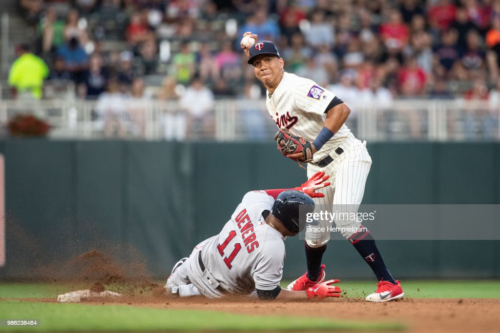 Ehire Adrianza #16 of the Minnesota Twins throws over Rafael Devers #11 of the Boston Red Sox on June 20, 2018 at Target Field in Minneapolis, Minnesota. The Twins defeated the Red Sox 4-1.