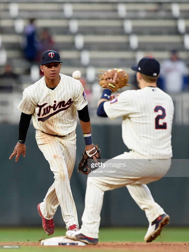 Ehire Adrianza #16 of the Minnesota Twins tosses the ball to teammate Brian Dozier #2 to start a double play against the Kansas City Royals during the eighth inning of game two of a doubleheader on May 21, 2017 at Target Field in Minneapolis, Minnesota. The Twins defeated the Royals 8-4.
