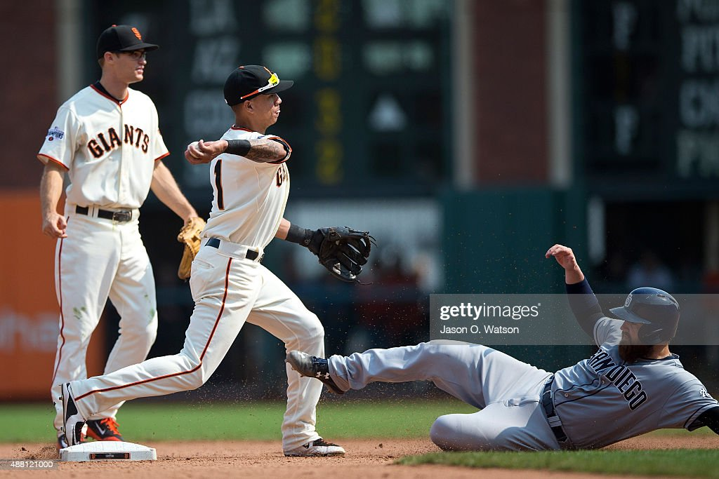 Ehire Adrianza #1 of the San Francisco Giants completes a double play over Derek Norris #3 of the San Diego Padres during the seventh inning at AT&T Park on September 13, 2015 in San Francisco, California. The San Francisco Giants defeated the San Diego Padres 10-3.