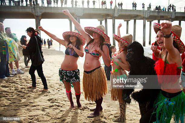 Ehryn McNulty left Melissa Pepper Jessica Stifller and Katie Kompara pose with other participants moments after running into the cold Pacific water...
