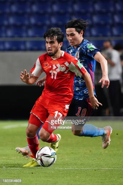 Ehson Panshanbe of Tajikistan controls the ball under pressure of Takumi Minamino of Japan during the FIFA World Cup Asian Qualifier 2nd round Group...