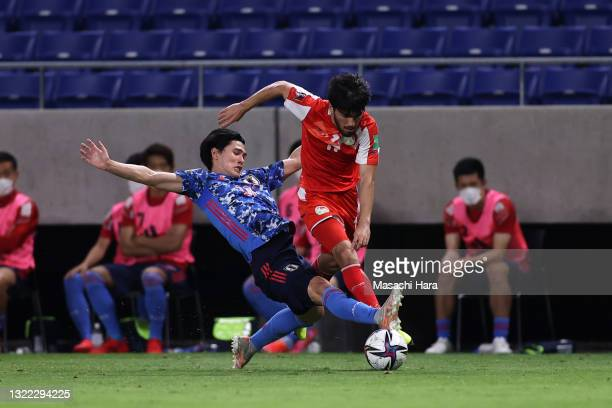 Ehson Panshanbe of Tajikistan is tackled by Takumi Minamino of Japan the FIFA World Cup Asian Qualifier 2nd round Group F match between Japan and...