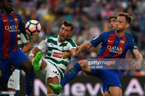Eibar's forward Sergi Enrich vies with Barcelona's defender Brazilian Defender Marlon and Barcelona's Croatian midfielder Ivan Rakitic during the...