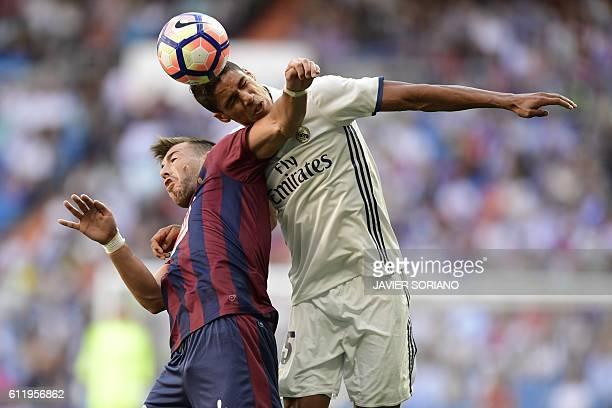 TOPSHOT Eibar's forward Sergi Enrich vies with Real Madrid's French defender Raphael Varane during the Spanish league football match Real Madrid CF...