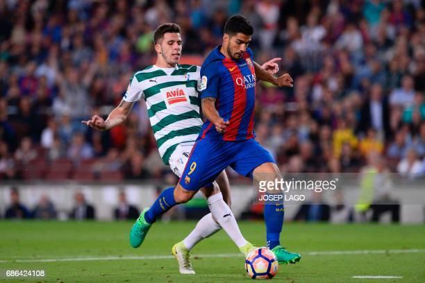 Eibar's midfielder Christian Rivera vies with Barcelona's Uruguayan forward Luis Suarez during the Spanish league football match FC Barcelona vs SD...