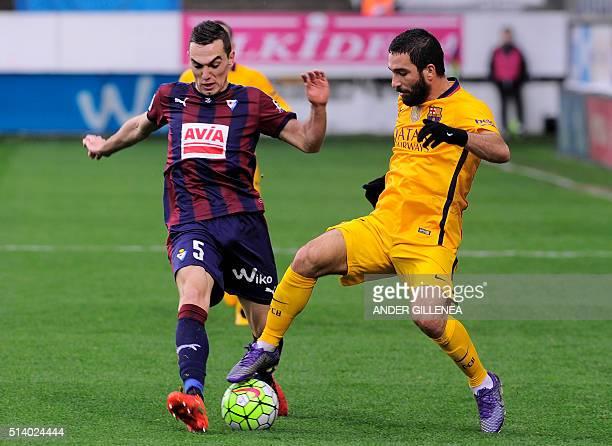 Eibar's midfielder Gonzalo Escalante vies with Barcelona's Turkish midfielder Arda Turan during the Spanish league football match SD Eibar vs FC...