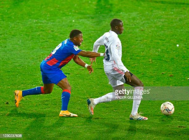 Eibar's Senegalese midfielder Pape Diop challenges Real Madrid's French defender Ferland Mendy during the Spanish league football match between SD...