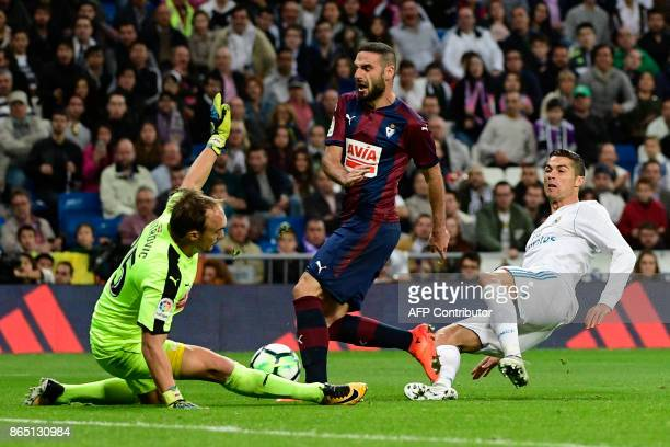 Eibar's Serbian goalkeeper Marko Dmitrovic and Eibar's Spanish defender David Lomban block a shot on goal by Real Madrid's Portuguese forward...