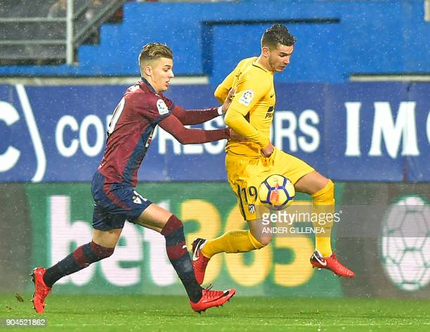 Eibar's Spanish midfielder Ivan Alejo vies with Atletico Madrid's French defender Lucas Hernandez during the Spanish league football match between SD...