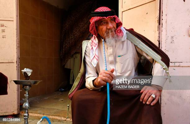 Eid Jaabari a Palestinian man wearing a traditional keffeyah on his head smokes a waterpipe in the old city of Hebron on May 8 2017 in the Israeli...