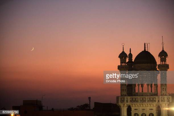 Eid-al-Fitr moon in sky and beautifully lit tomb of Masjid in textile town of Malegaon, Maharashtra, India