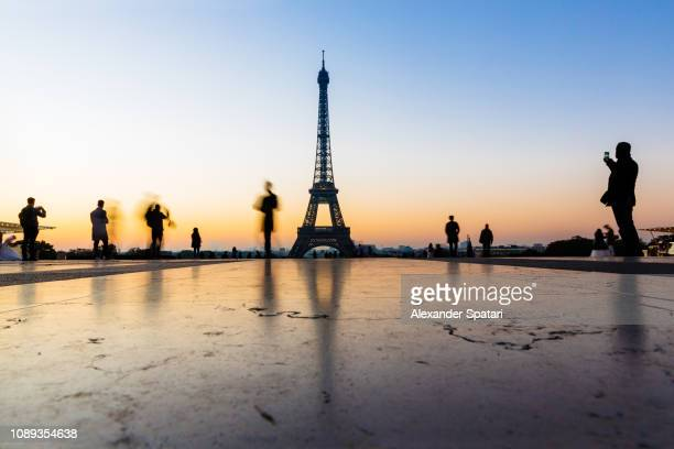 eiffel tower and people silhouettes at sunrise, paris, france - europa occidental fotografías e imágenes de stock