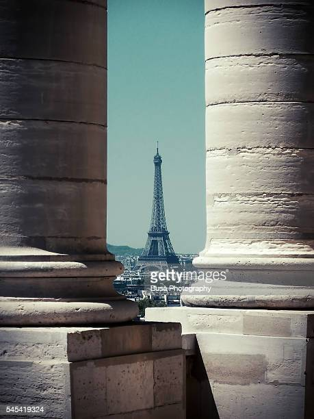 Eiffel Tower framed by two columns of the Palais du Trocadero across the Seine river. Paris, France