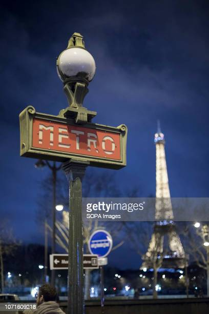 Eiffel Tower illuminated seen in the night with a Metro subway sign in Paris
