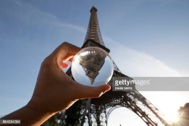 Eiffel tower is reflected over a glass ball