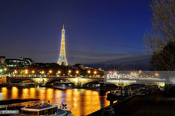 Eiffel Tower Pont des Invalides and Seine River bank in Paris at night seen from Pont Alexandre III