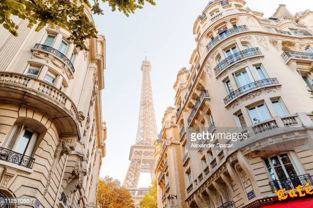 eiffel tower seen in the end of the street in paris, france - international landmark stock pictures, royalty-free photos & images