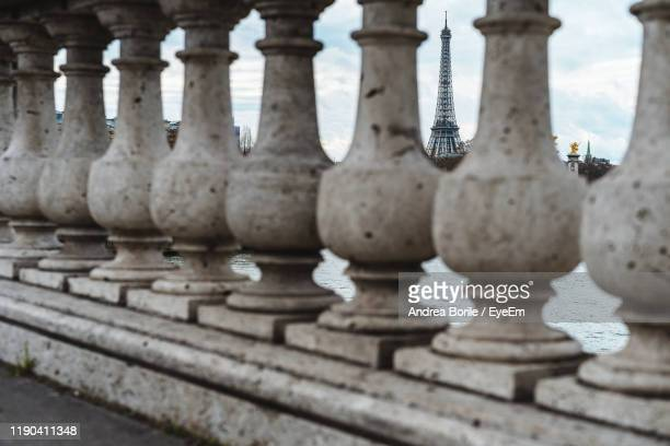 eiffel tower seen though stone railing - paris rocks stock pictures, royalty-free photos & images