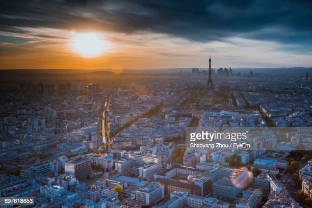 Eiffel Tower With Cityscape Against Cloudy Sky During Sunset