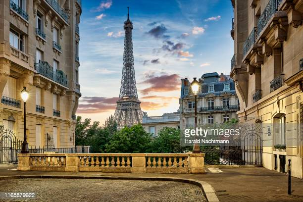eiffel tower with haussmann apartment buildings in foreground, paris, france - paris france photos et images de collection