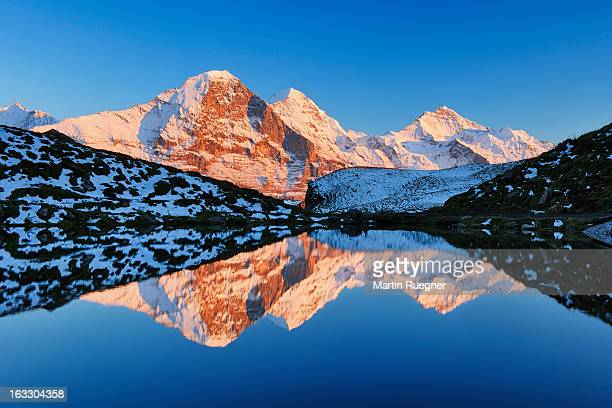 Eiger, Mönch and Jungfrau reflecting in pond.