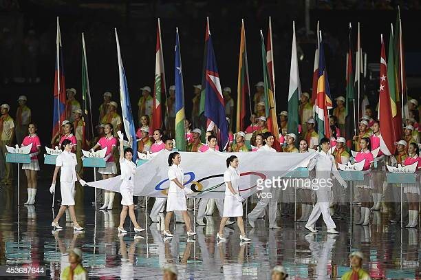 Eight athletes of China enter the stadium with the Olympic flag during the opening ceremony for the Nanjing 2014 Summer Youth Olympic Games at the...