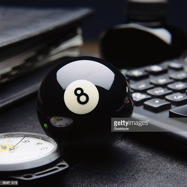 Eight ball on desktop, beside stopwatch, calculator and briefcase
