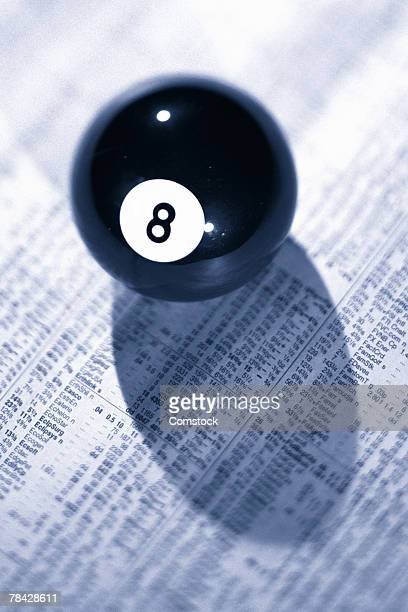 Eight ball on top of financial page of newspaper