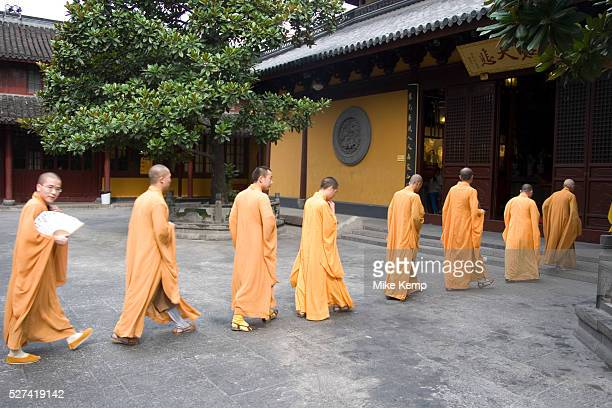 Eight Buddhist monks in ochre yellow robes walk from their quarters to one of their daily prayer sessions at Longhua Temple in the south of Shanghai...