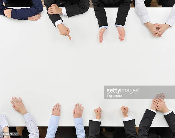 Eight business people having discussion on desk