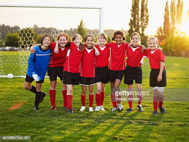 Eight female football players (10-11, 12-13) standing in pitch, arms around