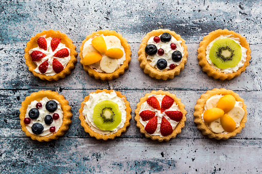 Eight mini pies with whipped cream garnished with different fruits - gettyimageskorea