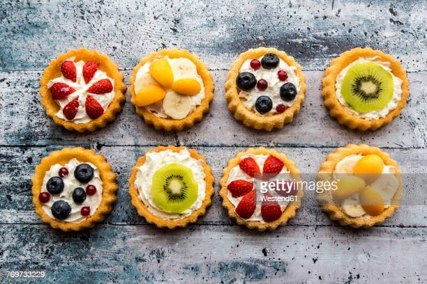 eight mini pies with whipped cream garnished with different fruits - fruit cake stock pictures, royalty-free photos & images