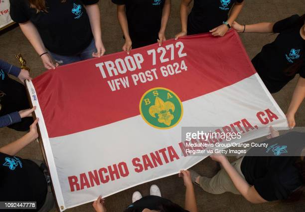 Eight of the 22 founding members of Boy Scout Troop 7272 stand around the new Troop flag for a portrait after a ceremony to submit an application for...