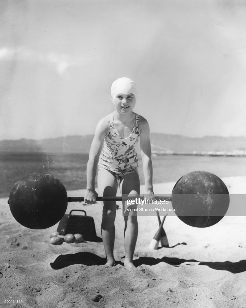 Eight year old Patricia O'Keefe, weighing 64 pounds, lifting heavy weights that adults could not even budge, Venice, California, early to mid 20th century.