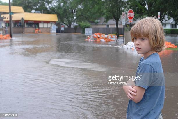 Eight year old Sammy Petersen watches as rising water ennundates the low lying area of the Czech Village June 11, 2008 in Cedar Rapids, Iowa. Several...