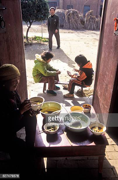 Eight year old school girl Xiao Chen plays a game of cards with a friend whilst her grandmother finishes off the lunch they have just enjoyed Chen's...