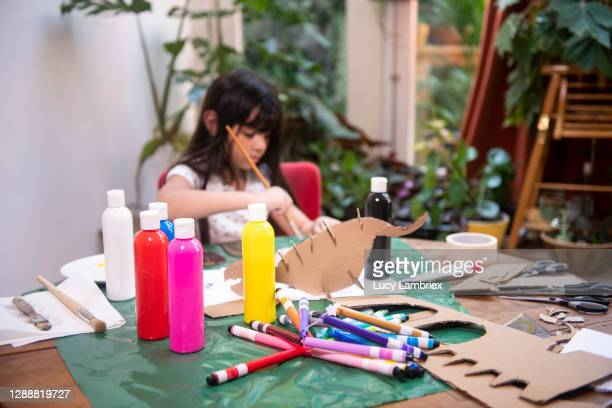 eight year old vlogger making a dinosaur from cardboard: painting the pieces - lucy lambriex stockfoto's en -beelden