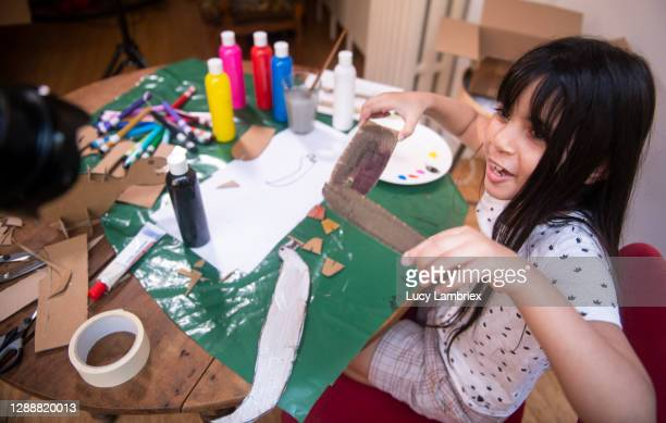 eight year old vlogger showing how to make a dinosaur from cardboard - 小道具 ストックフォトと画像