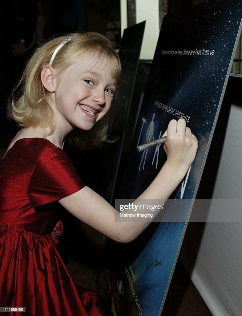 Eight year-old Dakota Fanning who is currently filming Dr. Seuss's Cat In the Hat has a major role in Steven Spielbergs Taken. The 20 hour mini-series premieres December 2, 2002 on the SCI FI Channel. Here Dakota signs one of the posters from the mini-series.