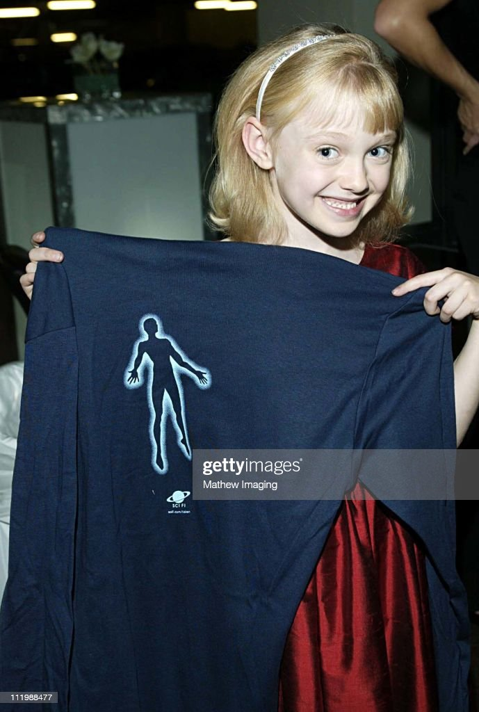 Eight year-old Dakota Fanning who is currently filming Dr. Seuss's Cat In the Hat has a major role in Steven Spielbergs Taken. The 20 hour mini-series premieres December 2, 2002 on the SCI FI Channel. Here Dakota shows off one of the shirts given out at the post premiere party.
