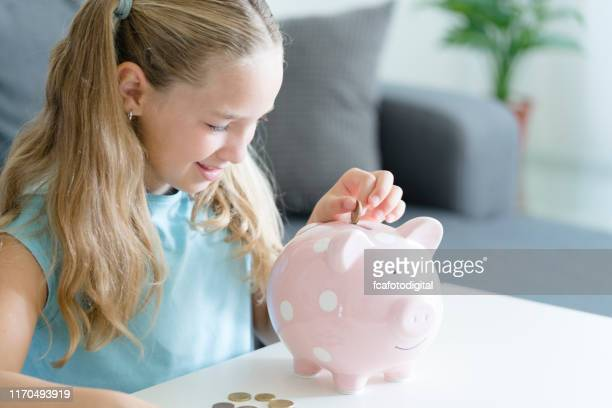 eight years old girl placing coins in her piggy bank. indoors shot. - 8 9 years stock pictures, royalty-free photos & images