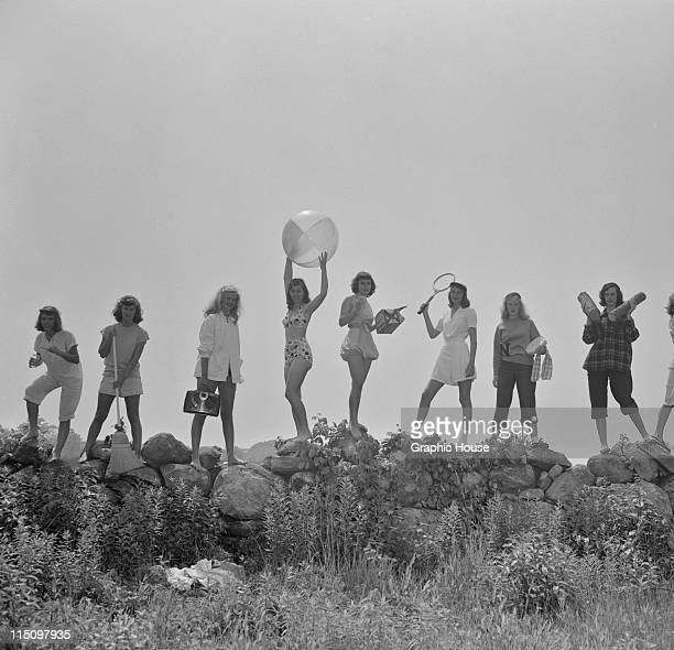 Eight young women in various poses and outfits stand in a row on top of a stone wall circa 1960